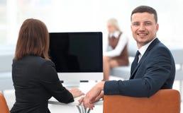 изолированная белизна вид сзади бизнесмен сидя на столе и смотря камеру Стоковое фото RF