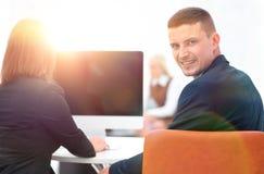 изолированная белизна вид сзади бизнесмен сидя на столе и смотря камеру Стоковые Изображения RF