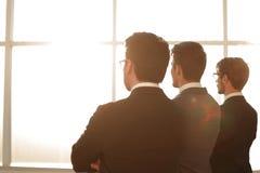 изолированная белизна вид сзади группа в составе бизнесмены смотря вне окно офиса Стоковые Фото