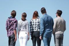 изолированная белизна вид сзади группа в составе молодые люди смотря космос экземпляра Стоковая Фотография