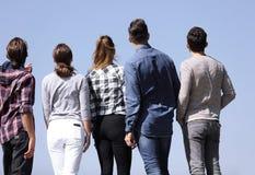изолированная белизна вид сзади группа в составе молодые люди смотря космос экземпляра Стоковые Фотографии RF