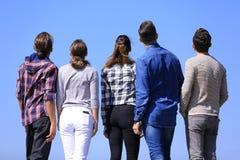 изолированная белизна вид сзади группа в составе молодые люди смотря космос экземпляра Стоковые Фото