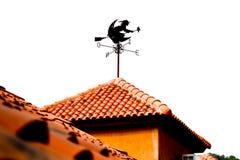 Изолированная лопасть ветра формы ведьмы на померанцовой крыше Стоковые Изображения