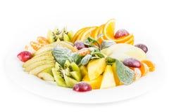 Изолированная плита плодоовощ, яблоко, мандарин, киви, виноградины, мята, груша, яблоко, ананас Фруктовый салат в конце-вверх пли Стоковая Фотография RF