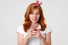 Изолированная съемка красивой усмехаясь женщины имбиря с очаровательной улыбкой, пользами современным мобильным телефоном, сообще стоковые изображения rf