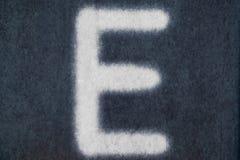 Изолированное e письмо мела в предпосылке классн классного Стоковая Фотография