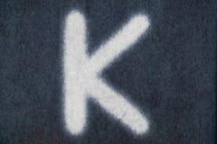 Изолированное k письмо мела в предпосылке классн классного Стоковое Фото