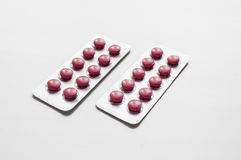 Изолированные красные пилюльки на белой предпосылке Стоковое Изображение