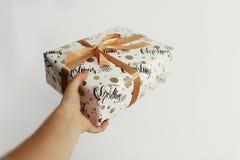 Изолированный белый подарок на рождество обернутый в бумажной и золотой нервюре Стоковые Изображения