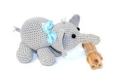 Изолированный вязать крючком крючком серый слон с голубым смычком на шеи стоит рядом с пуком деревянных карандашей на белой предп стоковое фото