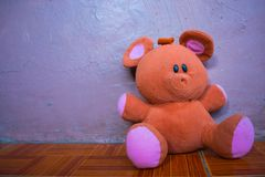 Изолированный мягкий пушистый Браун и розовая левая сторона плюшевого мишки кладя на пол стоковое изображение