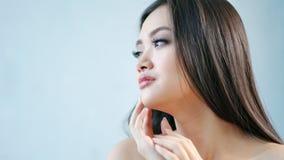 Изолированный портрет конца-вверх женщины красоты азиатской с чистой молодой кожей наслаждаясь и штрихуя подбородком сток-видео