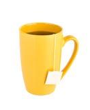 изолированный предпосылкой желтый цвет чая кружки белый стоковое фото