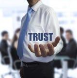 Изощренный бизнесмен держа доверие слова Стоковые Фото