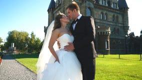 Изощренный жених и невеста целуя около замка Пары свадьбы идя в самый старый замок видеоматериал