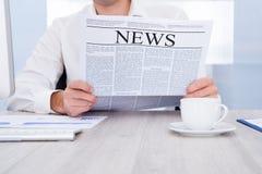 изолированная бизнесменом белизна чтения газеты Стоковое Изображение