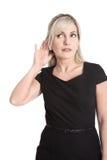 Изолированная бизнес-леди в черном платье слушая с слышать ai стоковое изображение