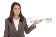 Изолированная бизнес-леди держа ключевой для партии новоселья внутри Стоковые Фото