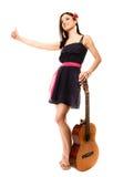 Изолированная девушка при гитара thumbing и пеший туризм заминкы Стоковые Фотографии RF