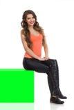 Изолированная девушка сидя на коробке зеленого Chroma ключевой стоковые фото