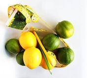 изолированная женщина веса торса измерения потери белая Измеряя лента обернутая вокруг лимонов Стоковые Изображения