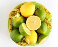 изолированная женщина веса торса измерения потери белая Измеряя лента обернутая вокруг лимонов Стоковые Изображения RF