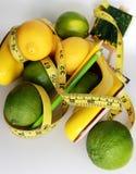 изолированная женщина веса торса измерения потери белая Измеряя лента обернутая вокруг лимонов Стоковое Изображение RF