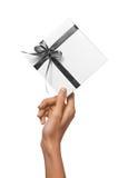 Изолированная женщина вручает держать коробку праздника присутствующую белую с серой лентой на белой предпосылке Стоковые Фотографии RF