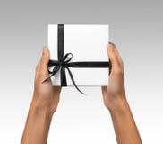 Изолированная женщина вручает держать коробку праздника присутствующую белую с лентой темной черноты на белой предпосылке Стоковое Изображение RF