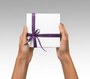Изолированная женщина вручает держать коробку праздника присутствующую белую с фиолетовой лентой на белой предпосылке Стоковые Изображения RF