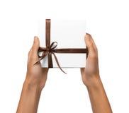 Изолированная женщина вручает держать коробку праздника присутствующую белую с лентой Брайна на белой предпосылке Стоковые Фото