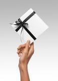 Изолированная женщина вручает держать коробку праздника присутствующую белую с лентой темной черноты на белой предпосылке Стоковые Изображения