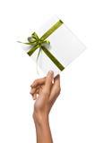 Изолированная женщина вручает держать коробку праздника присутствующую белую с зеленой лентой на белой предпосылке Стоковое Фото