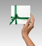 Изолированная женщина вручает держать коробку праздника присутствующую белую с зеленой лентой на белой предпосылке Стоковые Изображения RF