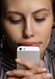 Изолированная женщина портрета молодая милая думая и держа phon Стоковое Изображение RF