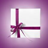 Изолированная коробка настоящего момента праздника белая с фиолетовой розовой лентой на предпосылке градиента Стоковые Изображения RF