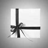 Изолированная коробка настоящего момента праздника белая с черной лентой на предпосылке градиента Стоковое фото RF