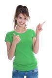 Изолированная прелестная девушка показывая и представляя с ее пальцем Стоковое фото RF