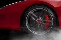 Изолированная родовая красная спортивная машина с деталью на колесе с красным цветом ломает перемещаться и курить на темной предп Стоковое фото RF