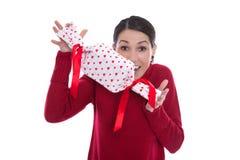 Изолированная смешная усмехаясь молодая женщина держа настоящий момент с красным цветом он стоковое фото