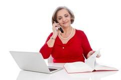 Изолированная старшая бизнес-леди в вызывать красного цвета - сидящ на столе стоковое изображение