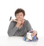 Изолированная старшая женщина - концепция денег с пенсионером ломать стоковая фотография