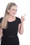Изолированная усмехаясь зрелая женщина в черный представлять платья стоковая фотография