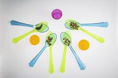 Изолированное разнообразие бобов на покрашенных пластичных ложках Стоковое фото RF