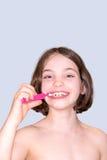 Изолированные зубы девушки чистя щеткой, стоковое изображение