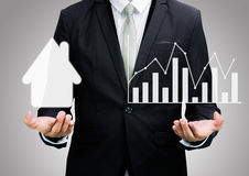Изолированные диаграмма и дом владением руки позиции бизнесмена стоящая Стоковое Фото