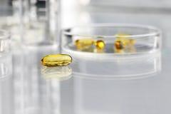 Изолированные пилюльки омега витаминов 3 дополнения с чашка Петри Стоковые Фотографии RF