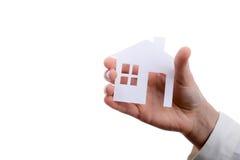 Изолированный бумажный дом в руке Стоковая Фотография RF