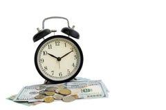 Изолированный будильник на наличных деньгах денег доллара и монетках - деле c стоковая фотография