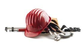 Изолированный красный трудный шлем с инструментами на белизне Стоковое Фото